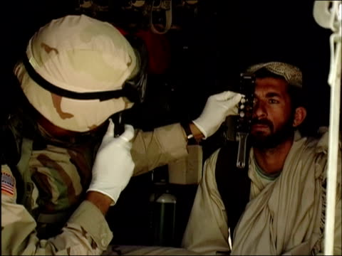 April 2004 Medium shot military doctor giving Afghan man an eye exam / Kandahar / AUDIO