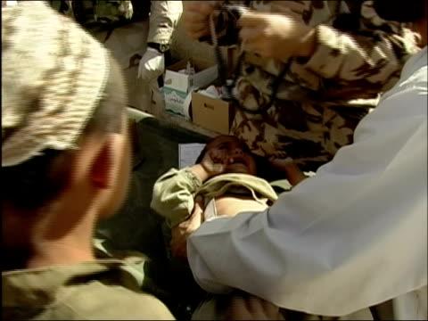 stockvideo's en b-roll-footage met april 2004 medium shot military doctors examining afghan baby / baby crying as boy holds him up / kandahar / audio - onderzoekstafel