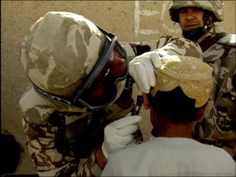 vídeos de stock e filmes b-roll de april 2004 medium shot romanian military doctor examining ear of young afghan boy / kandahar afghanistan / audio - kandahar