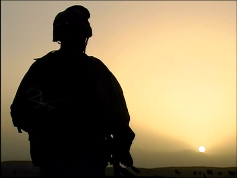 April 2004 rear view of armed US Army soldier watching sun set / Ghazni Afghanistan