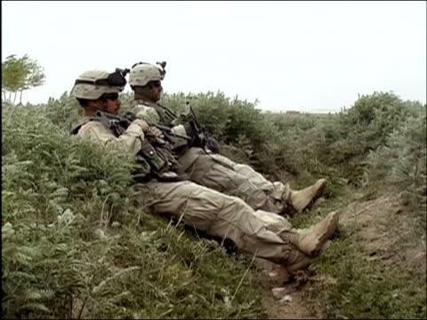 vídeos y material grabado en eventos de stock de april 2004 two armed us army soldiers reclining in ditch in field / ghazni, afghanistan - recostarse
