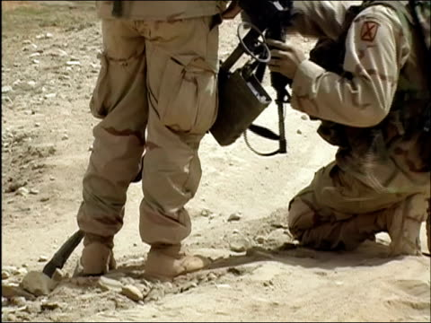 april 2004 us army eod soldiers digging hole in dirt road while sweeping for landmines / ghazni afghanistan - metal detector sicurezza video stock e b–roll