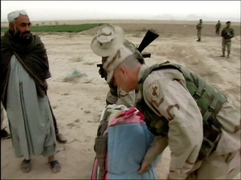 april 2004 us army major wes parker of 486th civil affairs battalion and us soldier bringing blankets to afghan villagers in kandahar province... - civilian stock videos and b-roll footage