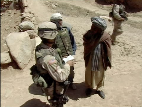 april 2004 us army soldier and afghan national army translator questioning civilian man about suspected insurgents / ghazni afghanistan - civilian stock videos & royalty-free footage