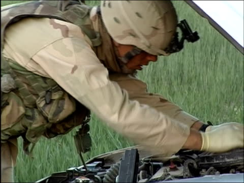 vidéos et rushes de april 2004 us army soldier inspecting engine of car at random security checkpoint on side of road in ghazni afghanistan - gant de chirurgie