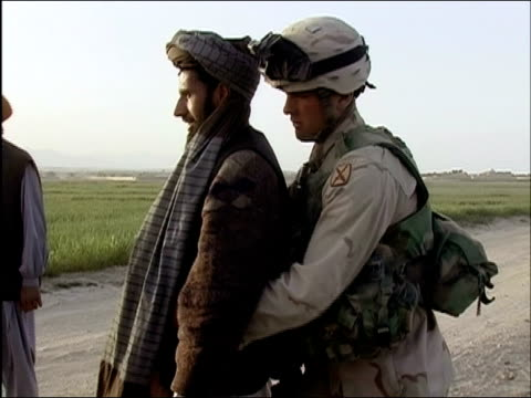 April 2004 US Army soldier patting down civilian man at random security checkpoint on road in Ghazni Afghanistan