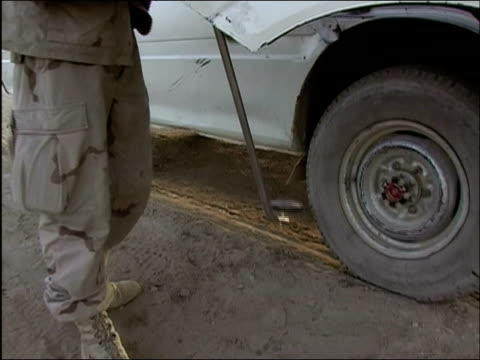 april 2004 us army soldier scanning suv with metal detector at random security checkpoint on road in ghazni afghanistan - metal detector sicurezza video stock e b–roll