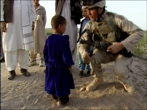 April 2004 US Army soldier scanning young boy with metal detector at random security checkpoint on road in Ghazni Afghanistan