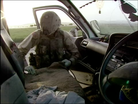 april 2004 us army soldier searching inside suv at random security checkpoint on road in ghazni, afghanistan - searching点の映像素材/bロール