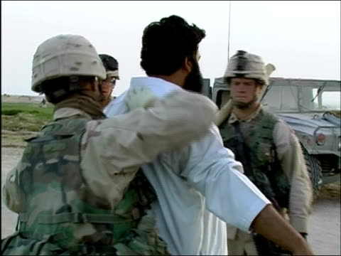 April 2004 US Army soldiers patting down civilian man at random security checkpoint on road in Ghazni Afghanistan