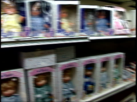 stockvideo's en b-roll-footage met april 25 1987 pan long store shelf stocked with baby dolls and doll accessories and correspondent charles krause pointing to merchandise while... - managua