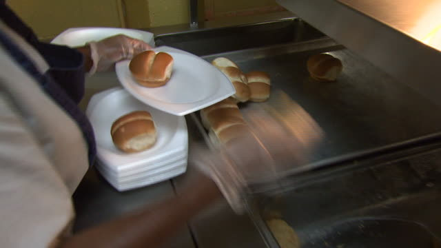 April 25 2010 PAN Lunch lady placing rolls on plates in the cafeteria / Marks Mississippi United States