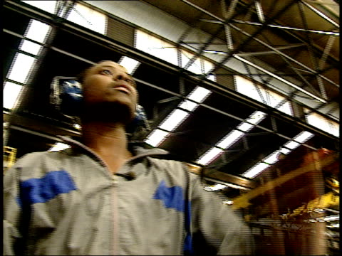 vídeos de stock e filmes b-roll de april 27, 1994 factory worker directing power lift moving metal tubes through factory warehouse interior / south africa - protetor de ouvido