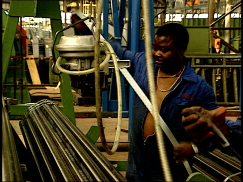 April 27 1994 TS Factory workers tying bundles of pipes with metal strips and moving overhead sealer / South Africa