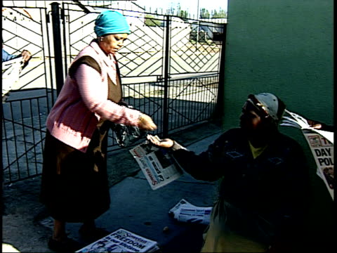 april 27 1994 montage woman purchasing soweto newspaper during the first allrace election / johannesburg gauteng south africa - anno 1994 video stock e b–roll