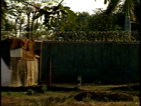 stockvideo's en b-roll-footage met april 28 1987 zo small shotgun shacks on the side of the road behind fence topped with barbed wire / managua nicaragua - managua
