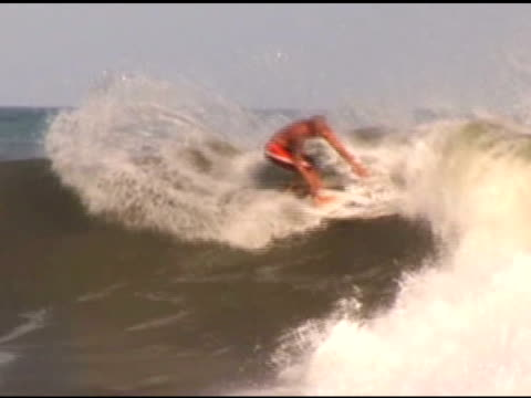 april 3, 2007 surfer doing back side snaps on face of wave and riding the tube / puerto escondido, oaxaca, mexico - letterbox format stock videos & royalty-free footage