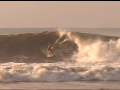 april 3, 2007 surfer doing backside snaps and bottom turns on wave face and riding the tube / puerto escondido, oaxaca, mexico - letterbox format stock videos & royalty-free footage
