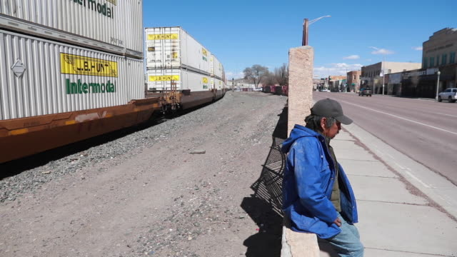 vidéos et rushes de a man sits nearby as a bnsf train passes through gallup along route 66 in gallup nm friday april 3 2020 - route 66