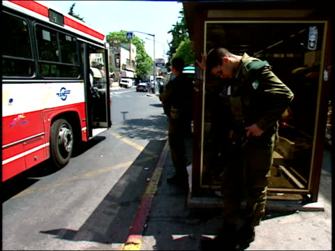 vidéos et rushes de april 30 1992 ts israeli soldiers carrying weapons stand guard at bus stop as bus arrives and passengers board / israel - israël