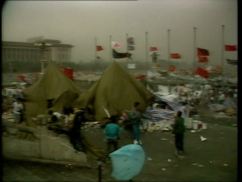 april in 1989 tiananmen square protests began beijing ext students secure rough shelters in square during windy weather / flags and banners blowing... - anno 1989 video stock e b–roll