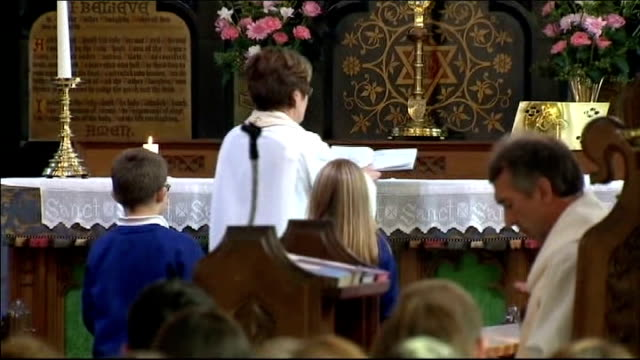 stockvideo's en b-roll-footage met church service held int high angle shot of two children walking up aisle with book dedicated to april rev rogers places book on altar gvs... - altaar