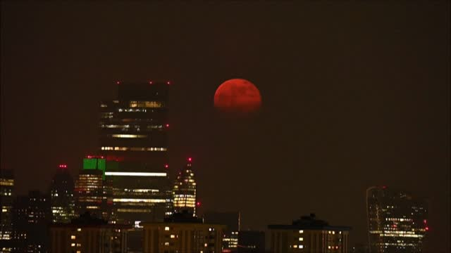 april's full moon, known as the super pink moon, rises over the london skyline - astronomy stock videos & royalty-free footage