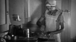 1936: Aproned women cooking in kitchen sifting flour for biscuits.