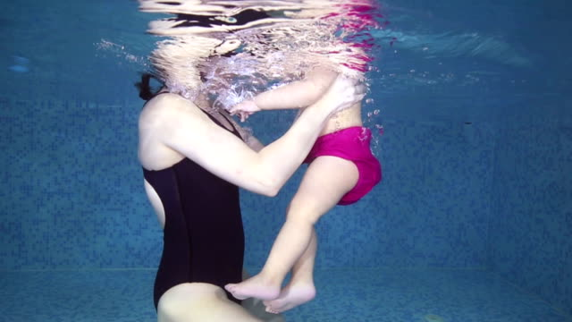 Aqua baby diving with her mother in to water