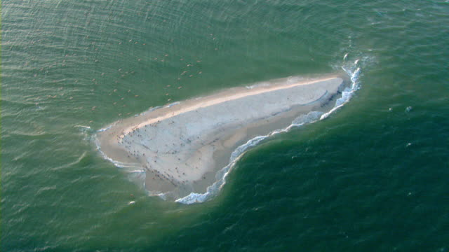 Aquamarine waters surround a small sandbar off the Mississippi coast.
