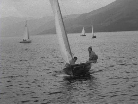 aquatics on loch earn; scotland: loch earn: ext pan yachts on loch in 'firefly' championship / yachts along / fv yacht / crew in yacht / two men... - グローワーム点の映像素材/bロール