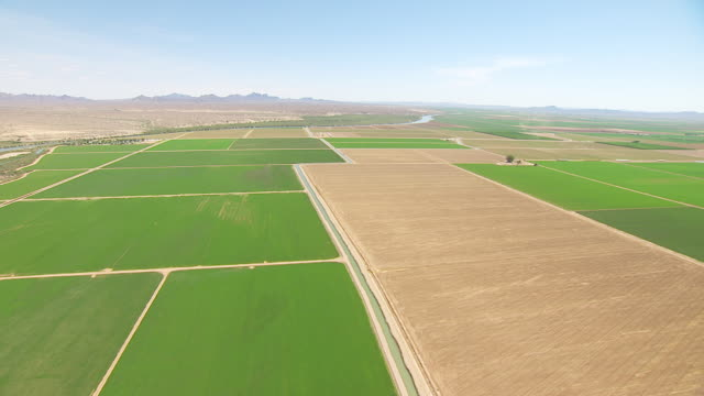 ws aerial pov aqueduct cutting through cultivated farmland bordered by the colorado river and desert with mountain ranges in distance / california, united states  - aqueduct stock videos and b-roll footage
