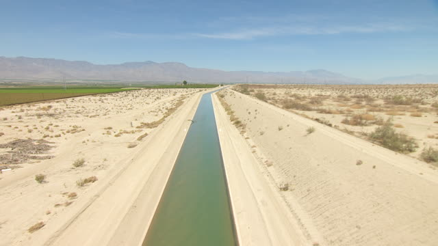 WS AERIAL POV Aqueduct winding through desert valley between sandy rocky foothills and cultivated farmland with mountains in distance / California, United States