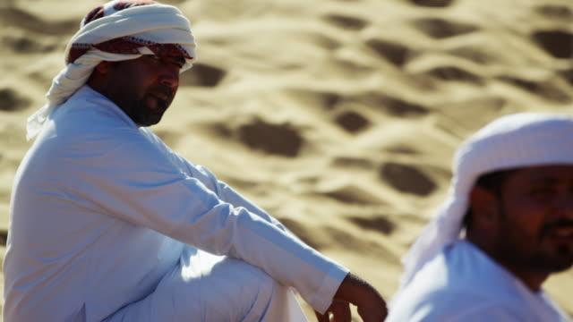vídeos de stock, filmes e b-roll de arab bedouin male resting camels in hot desert - adereço de cabeça