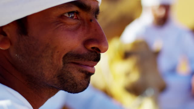 arab bedouin males in traditional dress leading camels - resting stock videos & royalty-free footage