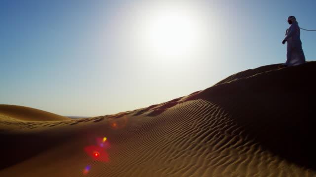 arab bedouin males in traditional dress leading camels - ベドウィン族点の映像素材/bロール