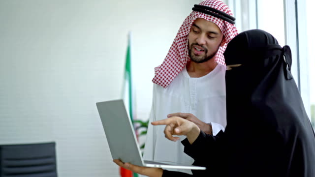 arab businessman and businesswoman using a laptop computer working at the office - gulf countries stock videos & royalty-free footage