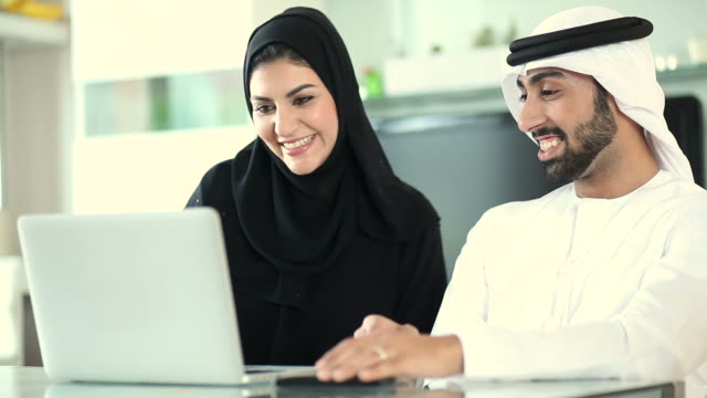 Arab Couple Planning Vacation Abroad Using Laptop
