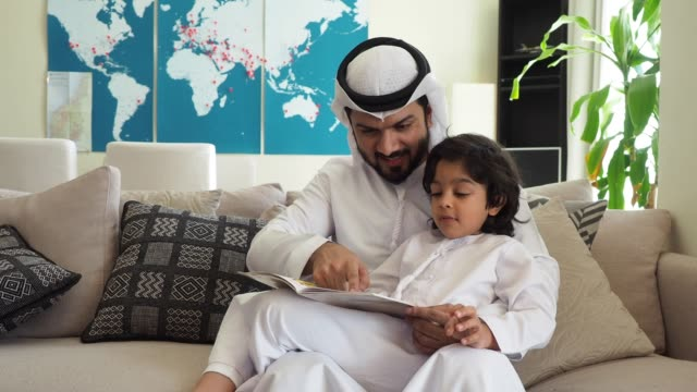 arab dad and son reading a book for homework at home - support stock videos & royalty-free footage