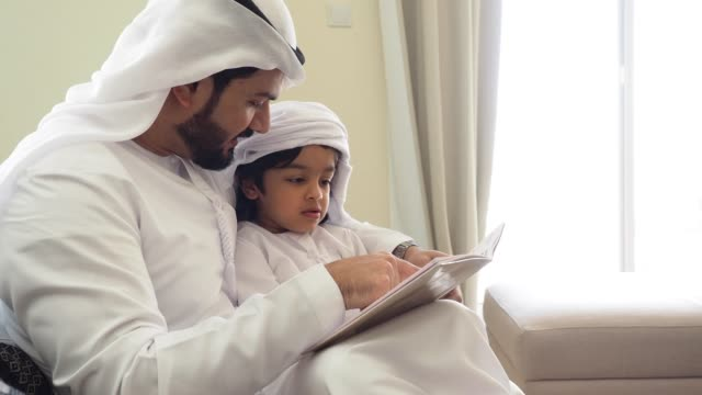 arab dad and son reading a book for homework at home - family stock videos & royalty-free footage