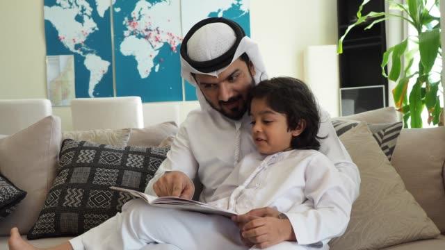 vídeos de stock e filmes b-roll de arab dad and son reading a book for homework at home - arabesco