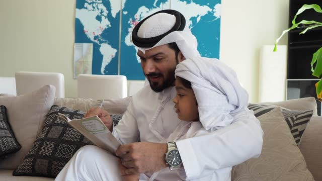 Arab dad and son reading a book for homework at home
