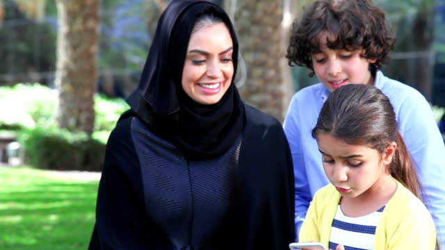 arab family enjoying with smartphone at park - islam stock videos & royalty-free footage