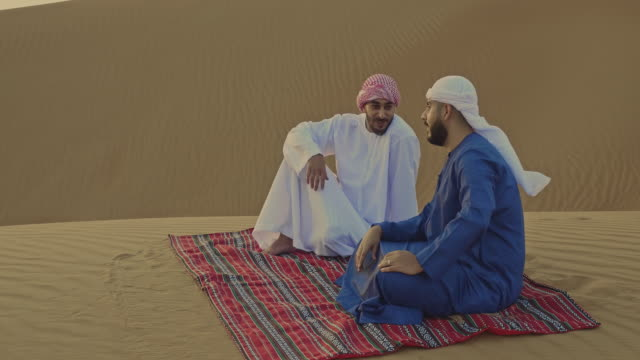 arab friends talking in the desert at sunset - clip stock videos & royalty-free footage