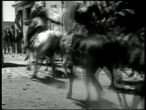 arab in crowd ms arabs on horses riding down street through gate ws arab soldiers running to row of legion tanks tents bg ms arabs climbing into tank... - 1948 stock-videos und b-roll-filmmaterial