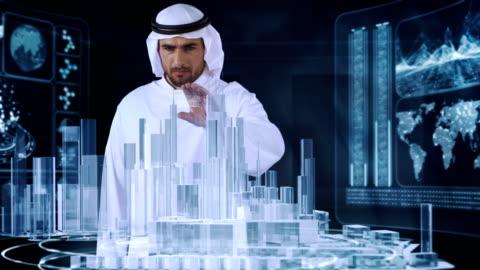vídeos y material grabado en eventos de stock de árabe en la ropa tradicional de trabajo con la realidad virtual. diseño de arquitectura urbana - holograma