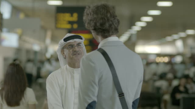 arab man at airport view of a middleaged bahraini man in traditional clothes in an airport terminal greeting and shaking hands with a european... - business person stock videos & royalty-free footage