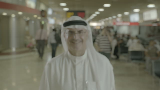 arab man at airport view of a middleaged bahraini man in traditional clothes standing in an airport terminal smiling to camera - dish dash stock videos & royalty-free footage