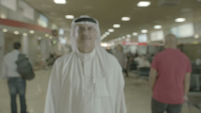 arab man at airport zoomin on a middleaged bahraini man in traditional clothes standing in an airport terminal grinning to camera - dish dash stock videos & royalty-free footage