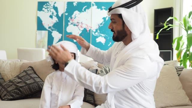 Arab man fixing keffiyeh to his son